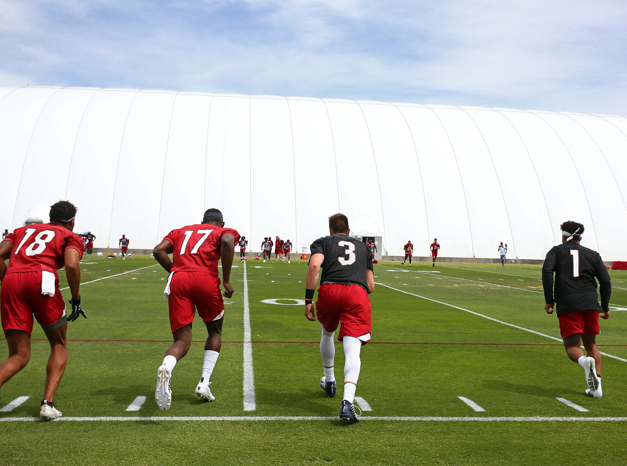 Cardinals quarterback Kyler Murray (1) and his teammates get warmed up before drills on the first day of rookie minicamp.