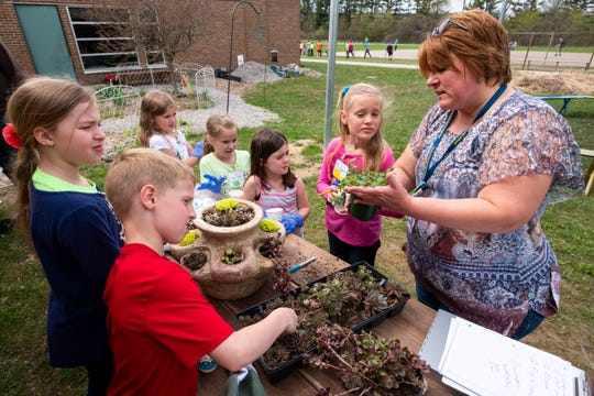 Memphis Community Schools substitute teacher Monique Werner teaches a group of students about different types of plants during an exercise at a Junior Naturalist Club meeting Thursday, May 9, 2019 at Memphis Elementary School.