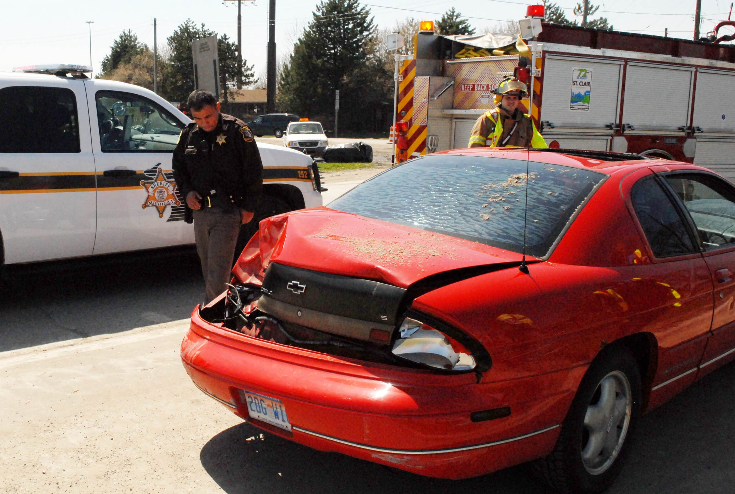 St. Clair County Sheriff Deputy Jacob Garza, left, and a Port Huron Township firefighter look over the damage to a car in 2011 on the Water Street I-94 over pass. Garza has been an analyst with the Detroit and Southeast Michigan Information and Intelligence Center for the last seven years.