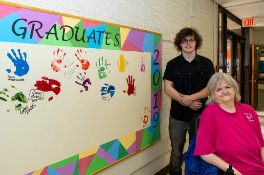 Cory Irvine, 17, left, and Delores Fallena, 76, stand near a sign where graduates will paint their handprints Thursday, May 9, 2019, inside the Harrison Center in Port Huron. After taking night classes, Fallena will be receiving her diploma, while Irvine will receive his GED this spring.