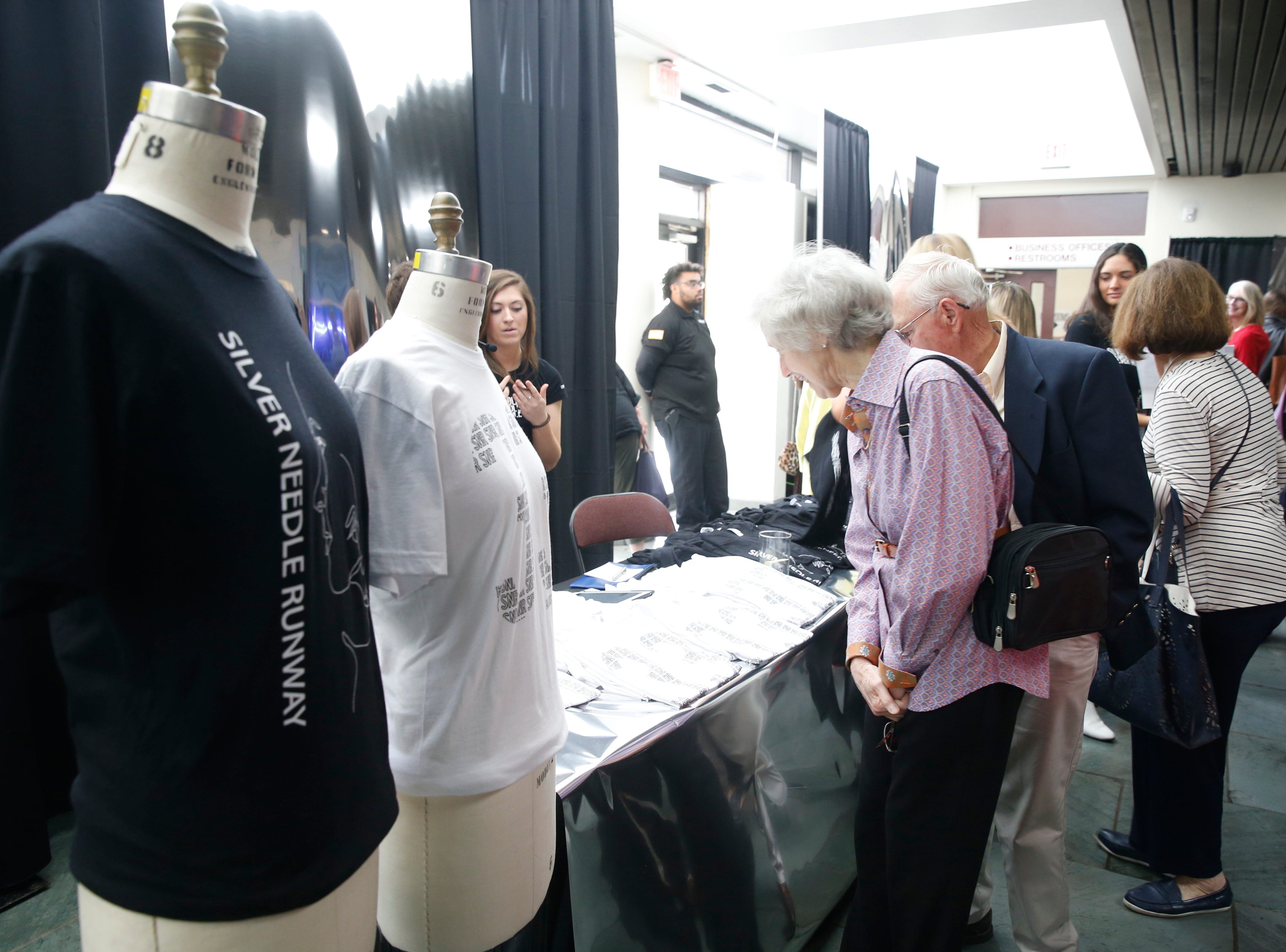 Susan and Jack Pretak of Hyde Park browse the merchandise tables before the start of the 33rd Marist College Silver Needle Runway Show on May 10, 2019.