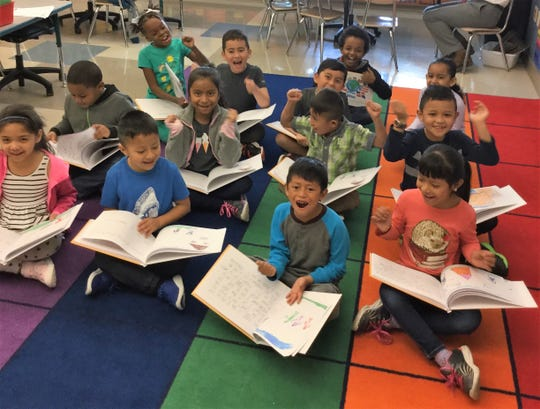 "Some of the 20 students in the ESL newcomer class at Benjamin Chambers Elementary show their published class book, ""Who We Are,"" which documents their journey learning English."