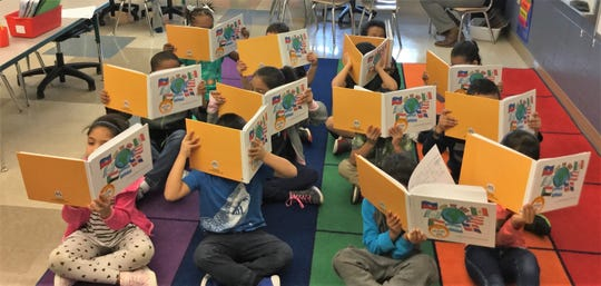"""Some of the 20 students in the ESL newcomer class at Benjamin Chambers Elementary show their published class book, """"Who We Are,"""" which documents their journey learning English."""