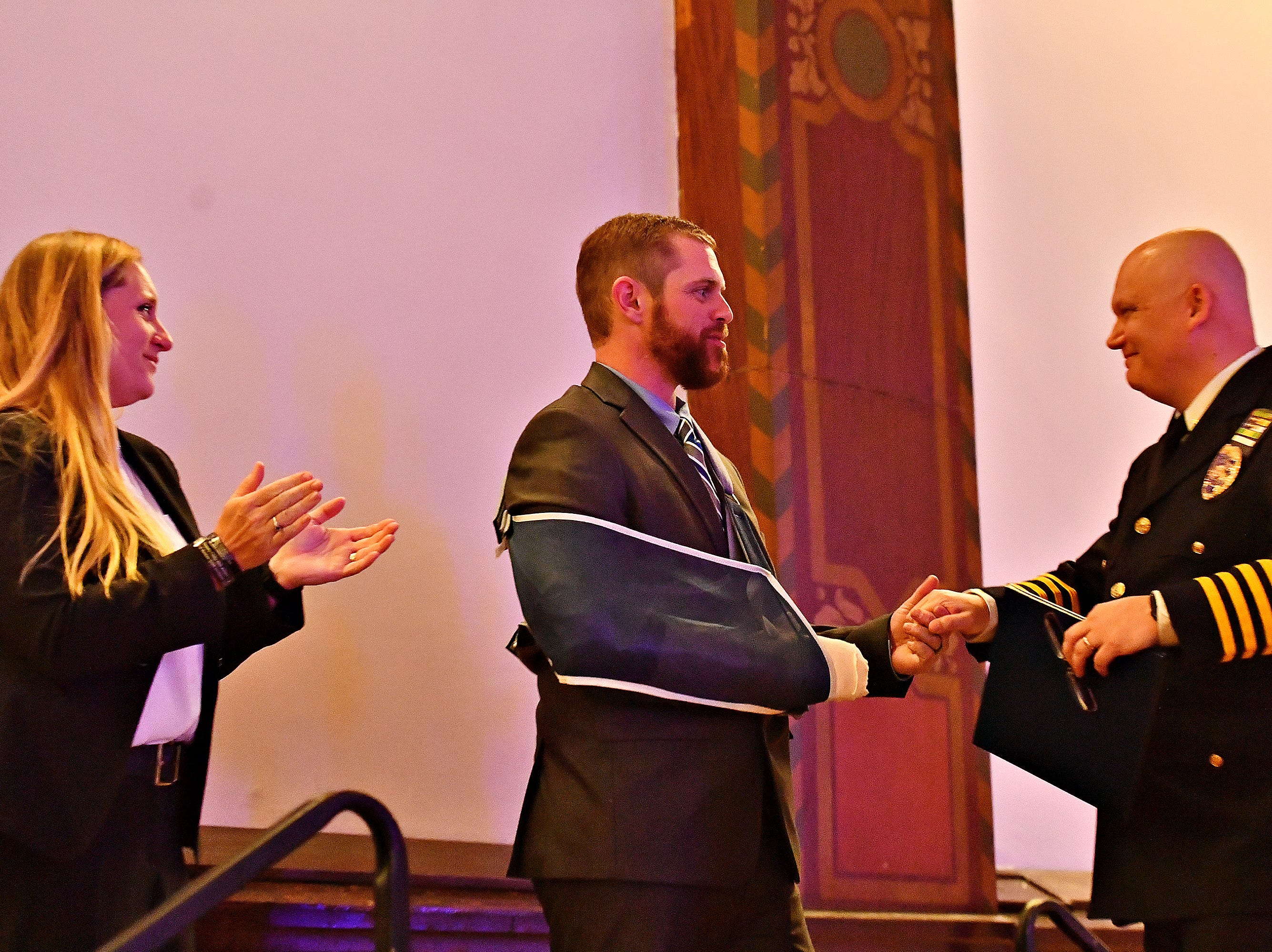 """From left, York City Det. Tiffany Pitts looks on as her husband, Police Officer Kyle Pitts, is presented with the 2018 """"Police Officer of the Year"""" award by York City Police Chief Troy Bankert during the York City Police Departmental Awards Ceremony at Valencia Ballroom in York City, Thursday, May 9, 2019. Dawn J. Sagert photo"""