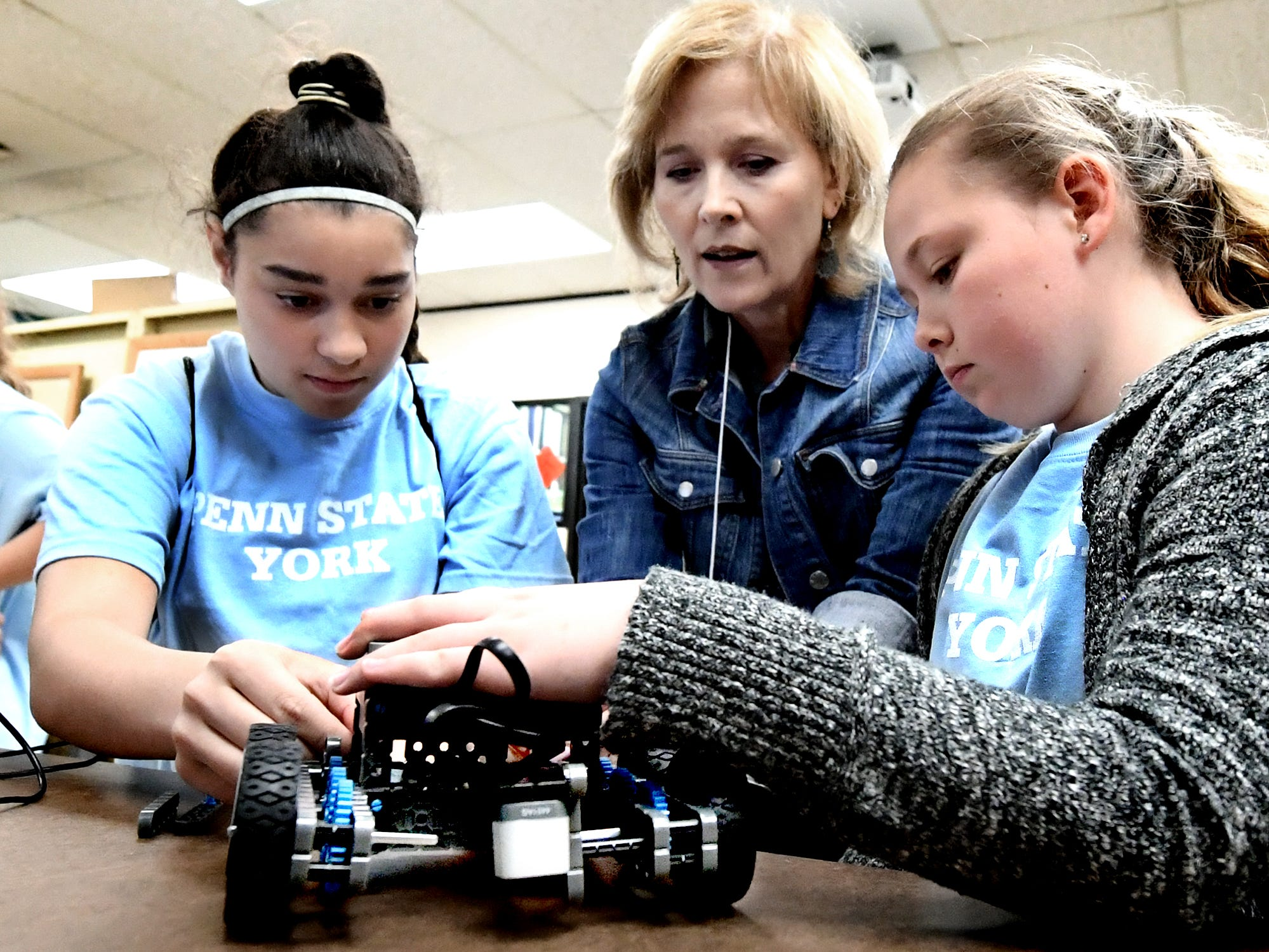 Penn State York engineering instructor Amy Harmon Krtanjek, center, works with Saint Theresa School students Samani Werner, left, and Alexus Browand during the Robogirl workshop at the Pathways to Your Future: Exploring STEAM Careers event at Penn State York Friday, May 10, 2019. Over 200 seventh-grade girls from 28 area schools participated in the program which highlighted science, technology, engineering, art, and mathematics (STEAM) careers. Industry leaders administered the workshops during the program, which is in its 23rd year. Bill Kalina photo