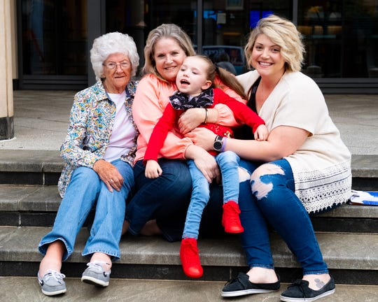 In the midst of great challenges through her life, Jo Anne Bennett (center) leans on her faith and humor. In this four-generation photo, Bennett is holding 4-year-old Ruby Hoffman, her granddaughter. Bennett's mother, Pat Grisham, is on the left, and Ruby's mom, Mindy Hoffman, is on the right., sitting on the steps of the York County Court House, May 9, 2019.