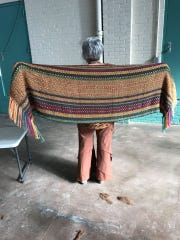 Beth Lutz, owner of Painted Spring Farm Alpacas in Jackson Township, standing with a shawl she recently made. Fiber from one of four alpacas killed on Lutz's farm in early April, was used to make the shawl.