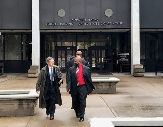 Former Rochester Housing Authority board Chairman George Moses, right, leaves federal court on Friday with his attorney, Frederick Hafetz.