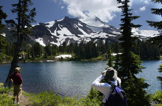 Hikers look out at Mt. Jefferson on Scout Lake in the Jefferson Park Wilderness.