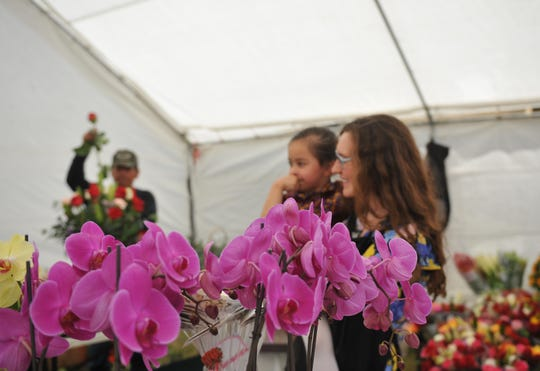 Laura Carrillo holds her niece while helping to sell Mother's Day flowers at Magda's Flowers stand on East Alisal Street May 10, 2019.