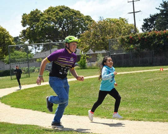 After riding in to cheers and applause, many Salinas Mountain Bike Team riders took to the blacktop and track field to run around with Roosevelt students.