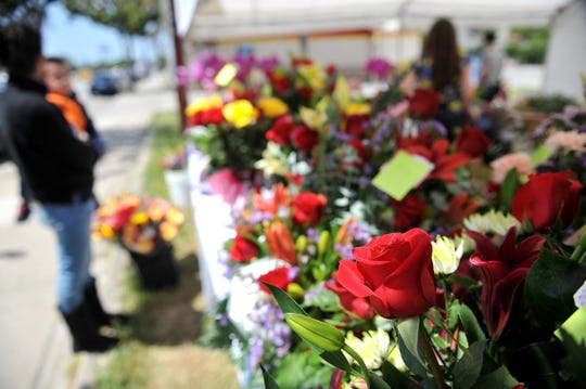 A woman and chidl look over flowers for Mother's Day at Magda's Flowers on East Alisal Street May 10, 2019.