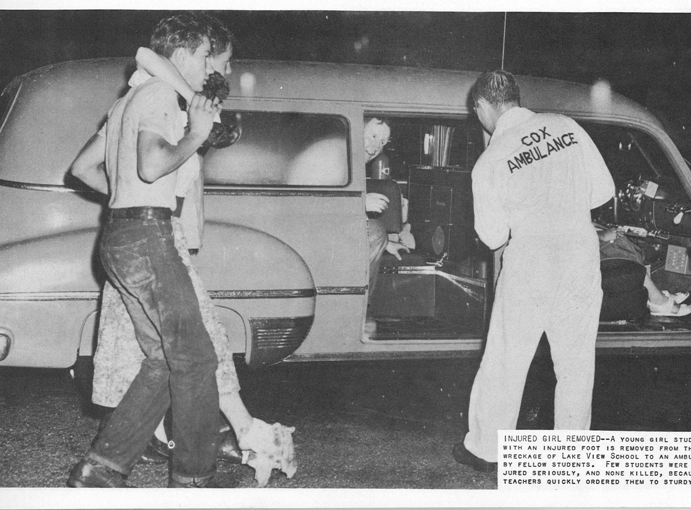 Though the Lake View tornado was devastating, residents stepped in to help their neighbors on May 11, 1953. The outline reads: A young girl student with an injured foot is removed from the wreckage of Lake View School to an ambulance by fellow students. Few students were injured seriously, and none killed, because teachers quickly ordered them to sturdy areas.