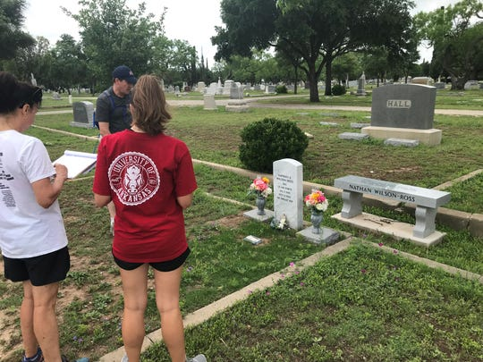 Vivian Yale and her parents, Camille and Ed Yale place and report a flag holder at a grave at Fairmount Cemetery, 1120 W. Ave. N. Sunday, May 5, 2019.