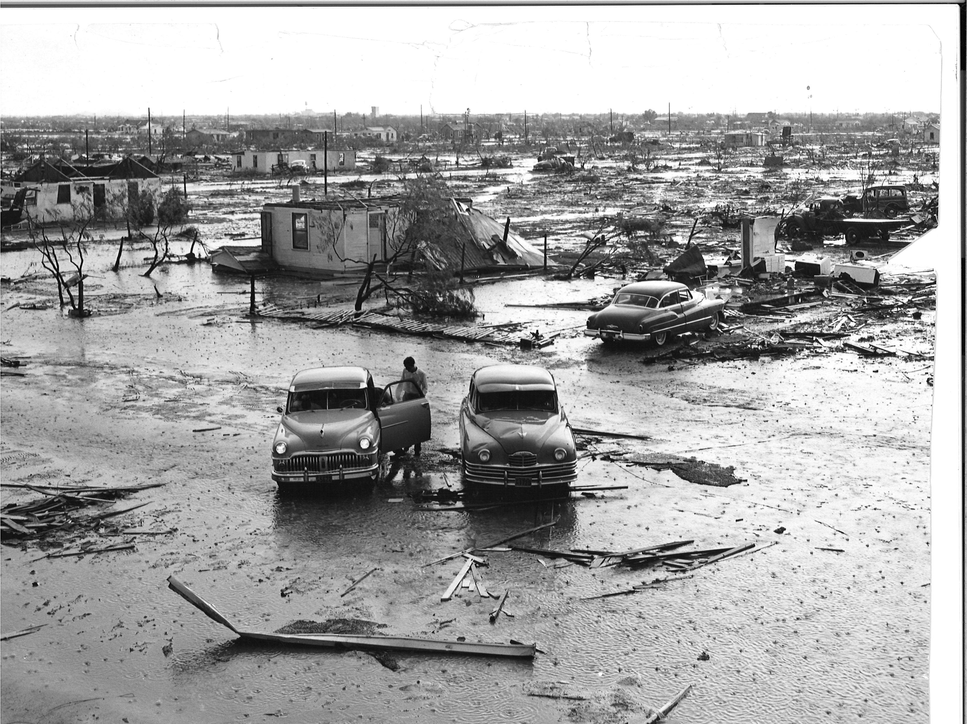 A person looks into their car after the Lake View tornado ripped through San Angelo on May 11, 1953. The original cut-line reads: Clean-swept area in center shows how entire blocks of Lake View were flattened. Car, right center, is parked in front of a house which only the floor, a piece of inner wall and a small chest remain. Foreground cars were not in storm.
