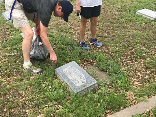 Ed Yale places a flag holder in the ground at Fairmount Cemetery,  1120 W. Avenue N., Sunday, May 9, 2019.