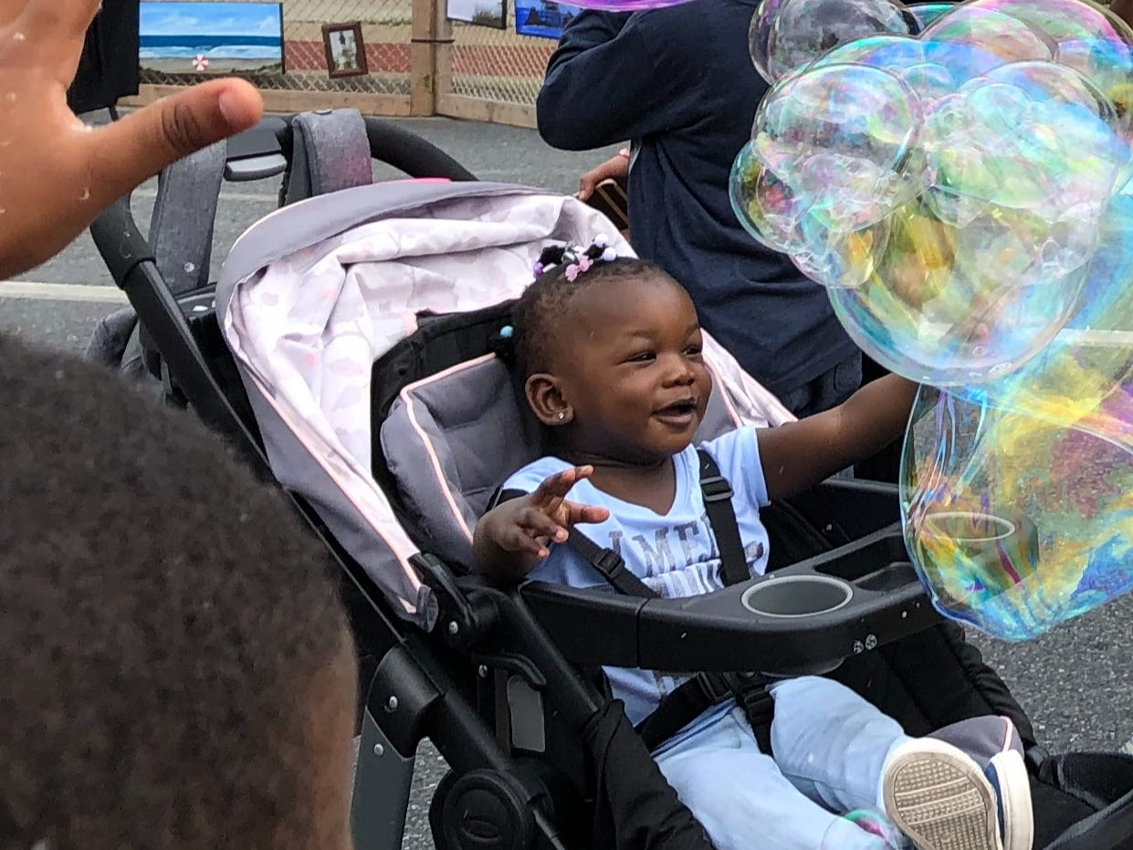 Temani Ameera Miller, age 1, was delighted by the bubbles at Street Fest in Princess Anne on May 4. Dozens of children filled Somerset Avenue to blow, chase and pop bubbles.