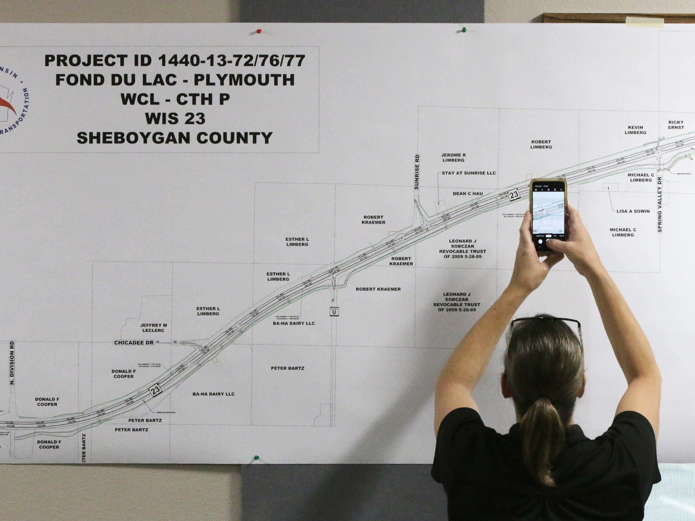 A woman snaps a photo of plans of the state Highway 23 four-lane construction project following a meeting at the Sheboygan County Transportation facility, Thursday, May 9, 2019, in Plymouth, Wis.
