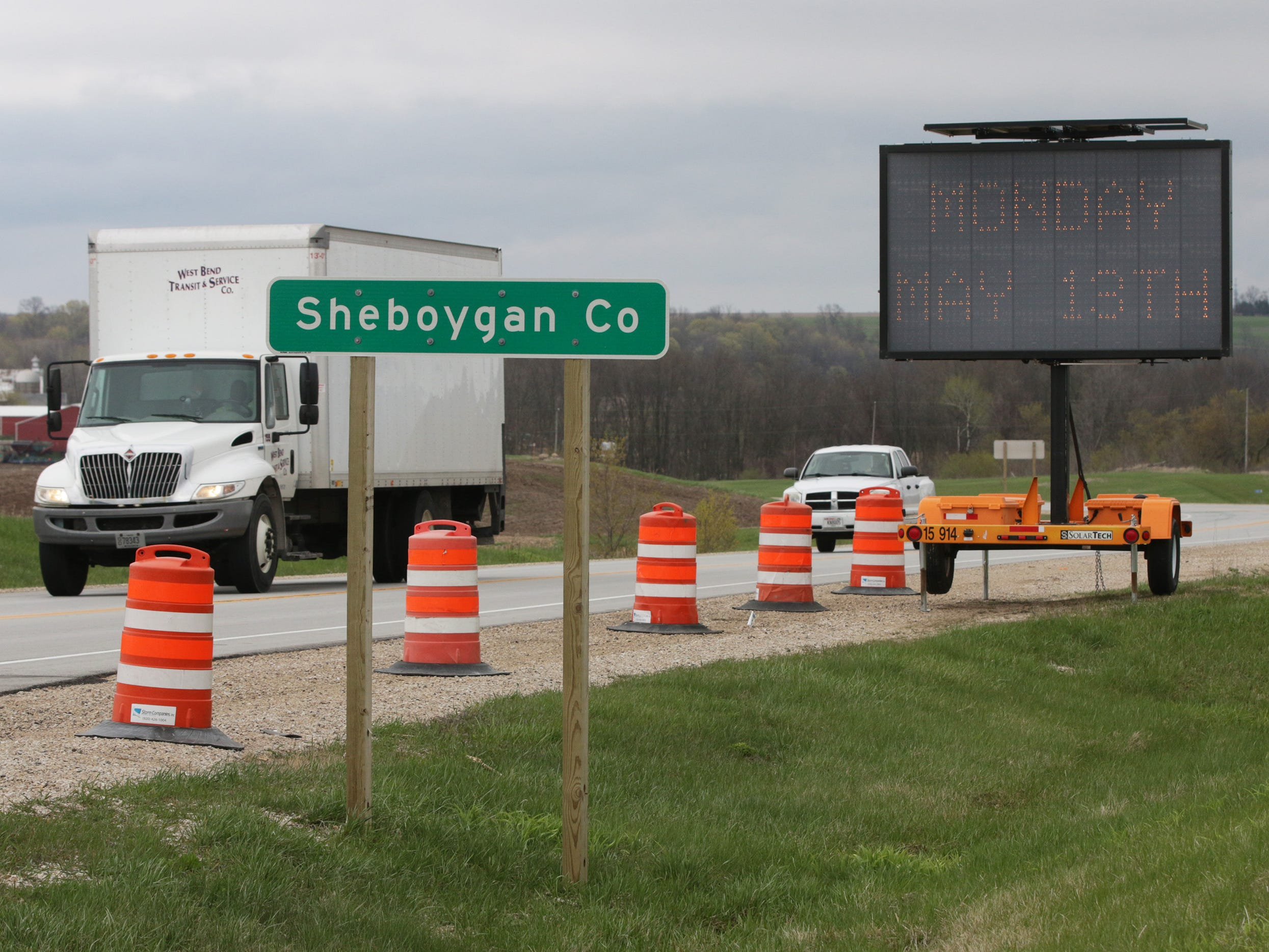 Vehicles travel west Thursday, 9, 2019, by signs warning of construction starting May 13 2019 near Greenbush, Wis.for the State Highway 23 four-lane construction project will start next week.