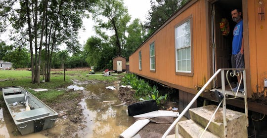 Douglas Ketchum stands in the doorway of his mobile home Friday, located on Cannon Road in Bossier Parish. He and his wife, Melinda, were rescued Thursday from flash flood waters that submerged most of their residential street.