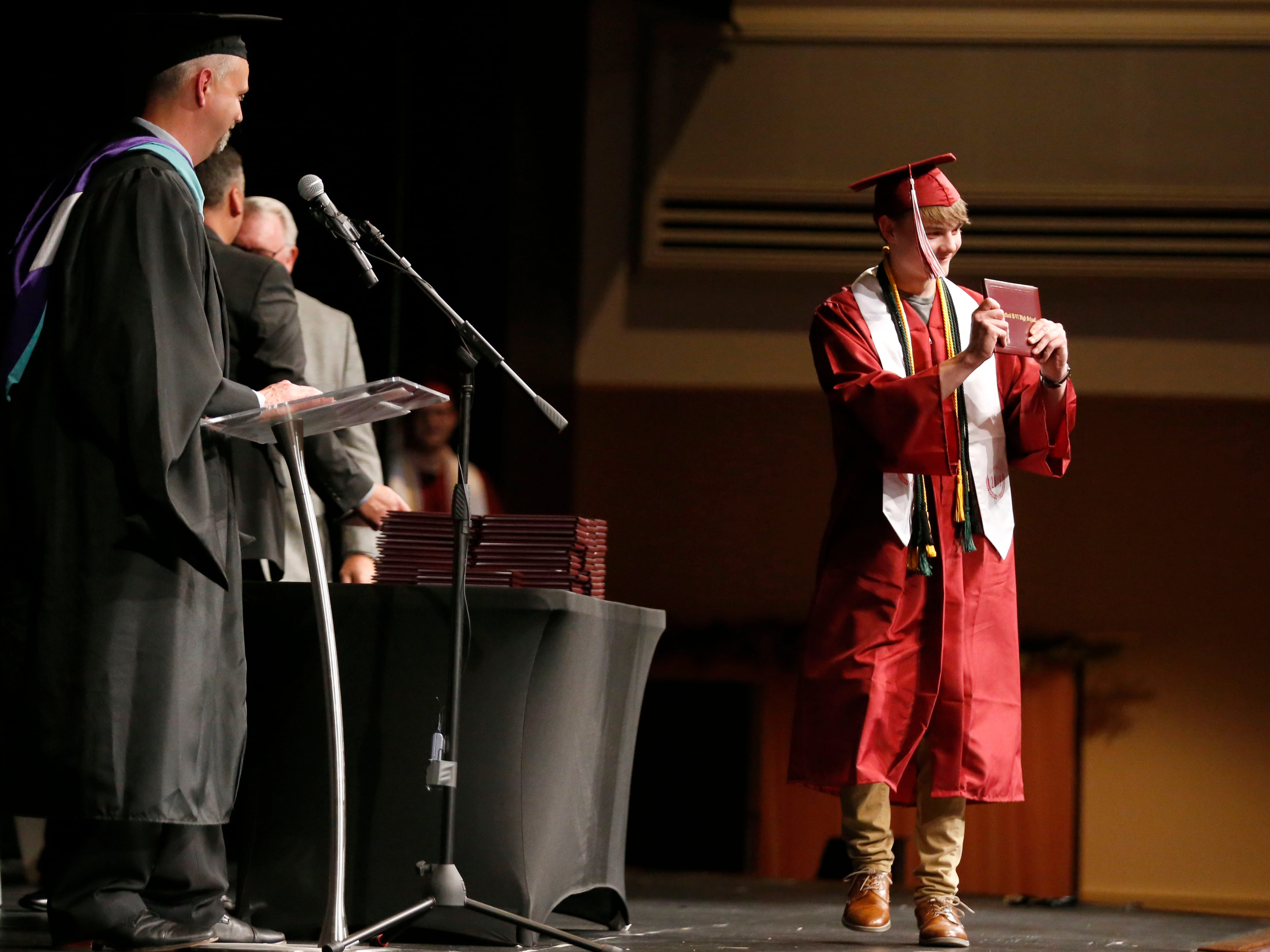 Joshua Luna shows off his diploma cover while crossing the stage during the Strafford High School Commencement Ceremony at High Street Baptist Church on Thursday, May 9, 2019.
