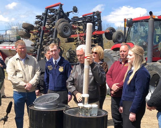 Vice President Mike Pence, center, holds a tube of soy beans Thursday as he tours the R & J Johnson Farms in Glyndon to talk about the Trump administration's trade agreement with Canada and Mexico.