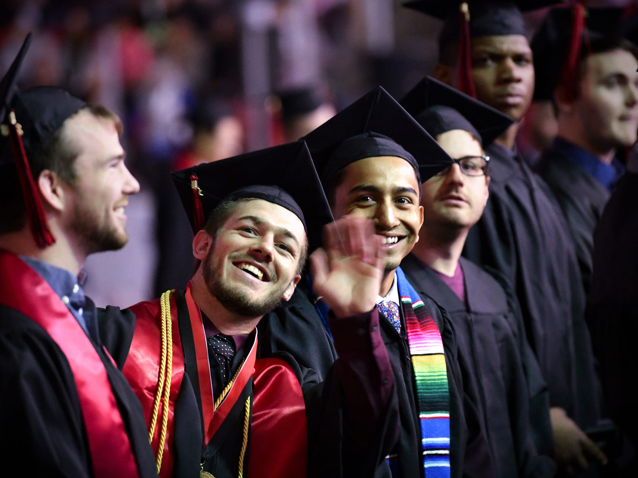 Students wave at friends and family in the audience during the morning commencement ceremony Friday, May 10, in the Herb Brooks National Hockey Center at St. Cloud State University in St. Cloud.
