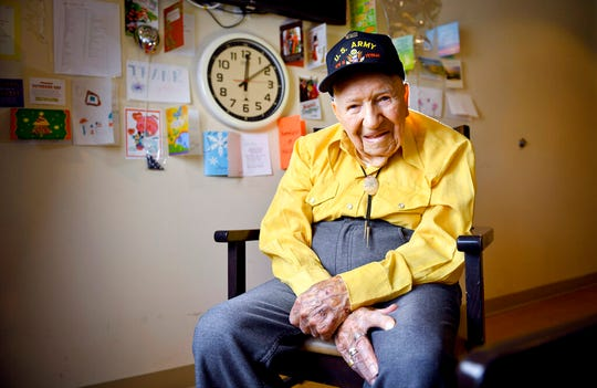 In this Monday, May 6, 2019, photo, John R. Frey, 100 years old and a U.S. Army veteran, poses for a portrait next to cards and mementos he has been given at the Mervyn Sharp Bennion Central Utah Veterans Home in Payson, Utah. Frey will turn 101 on June 7 of this year. (Isaac Hale/The Daily Herald via AP)