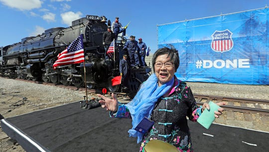 Margaret Yee, whose ancestors helped build the railroad, pose in front of the the Big Boy, No. 4014 during the commemoration of the 150th anniversary of the Transcontinental Railroad completion at Union Station Thursday, May 9, 2019, in Ogden, Utah. Yee, helped tap a ceremonial spike alongside Utah Gov. Gary Herbert and a descendant of Union Pacific's chief engineer on the project at the event Thursday in Ogden, Utah. (AP Photo/Rick Bowmer)