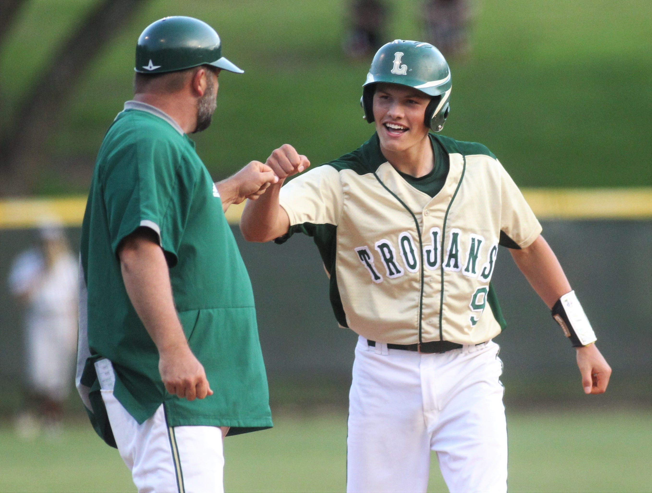Lincoln juniro Parker Wakeman fist bumps head coach Mike Gauger after reaching third base as Lincoln baseball beat Chiles 5-4  in 10 innings during a District 2-8A championship game on Thursday, May 9, 2019.