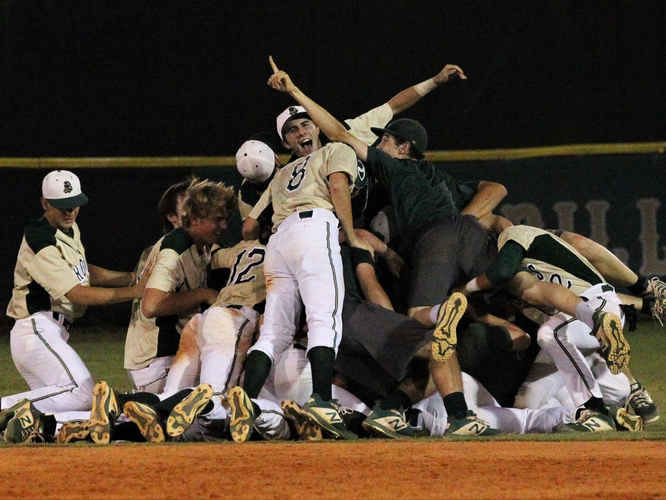 Lincoln baseball players dog-pile Justin Bragdon after a walk-off hit as the Trojans beat Chiles 5-4  in 10 innings during a District 2-8A championship game on Thursday, May 9, 2019.