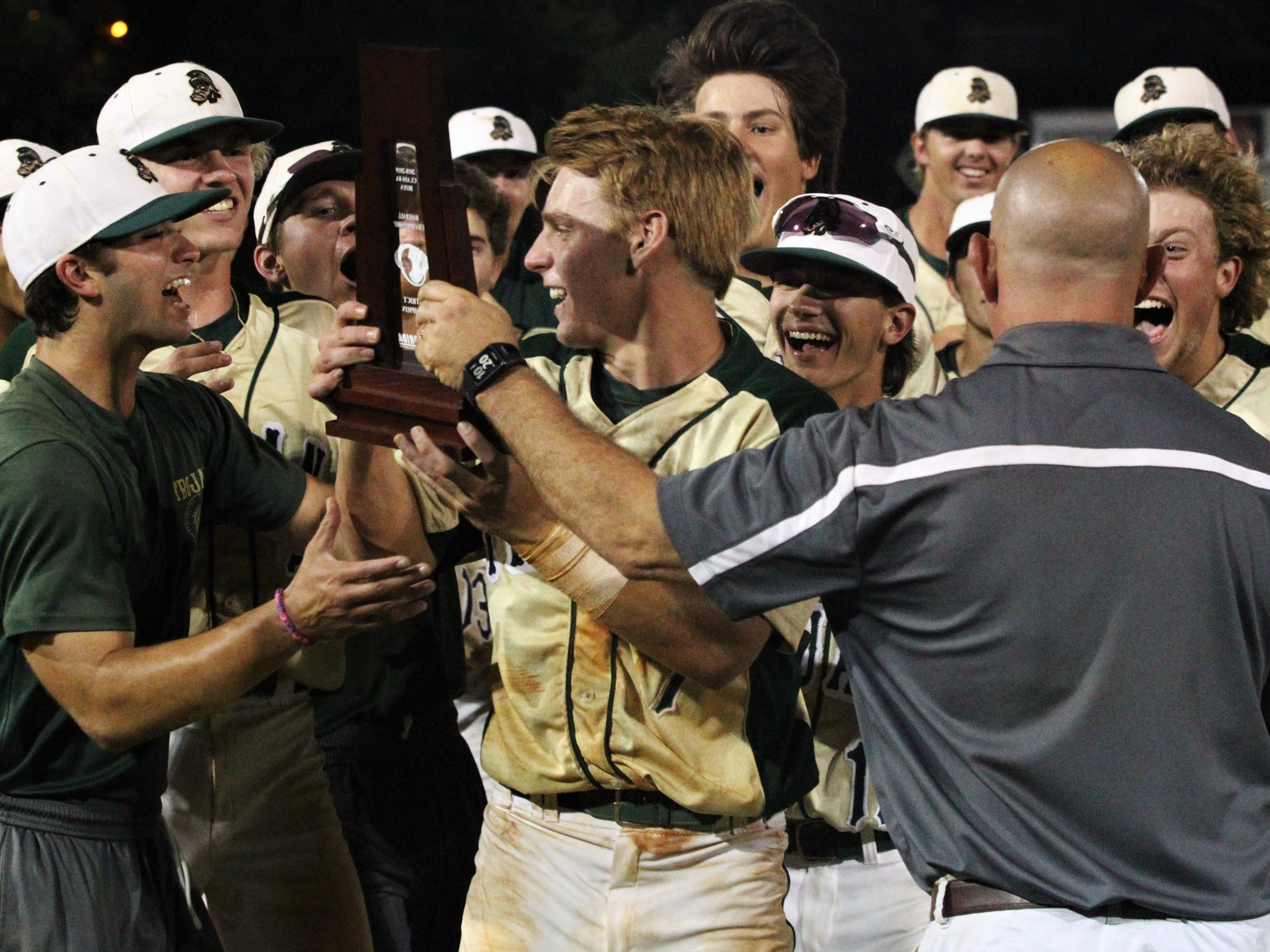Justin Bragdon gets handed the district championship trophy following his walk-off hit as Lincoln baseball beat Chiles 5-4  in 10 innings during a District 2-8A championship game on Thursday, May 9, 2019.