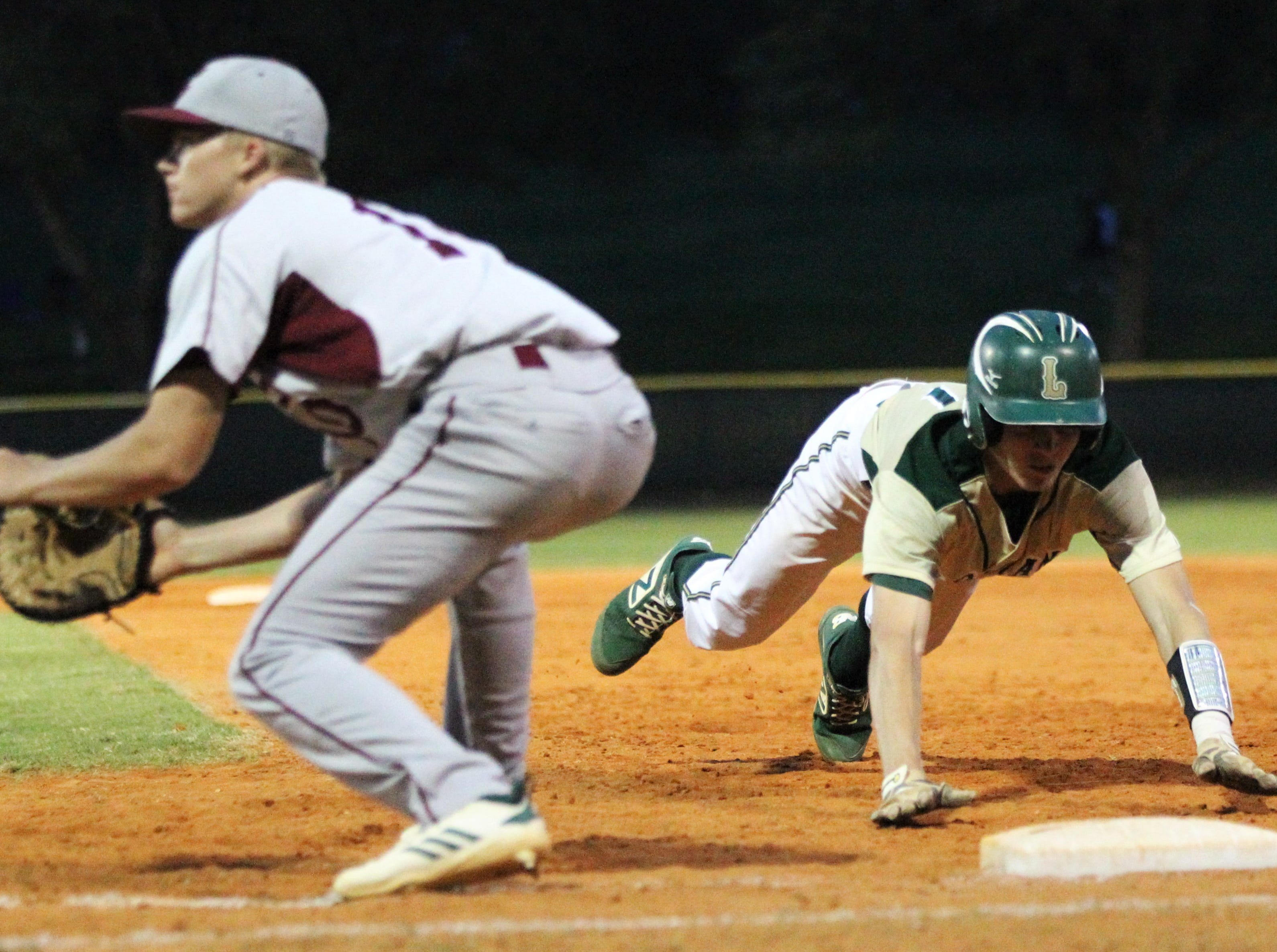 Lincoln senior Nick Standridge dives back into first on a pick-off attempt as Lincoln baseball beat Chiles 5-4  in 10 innings during a District 2-8A championship game on Thursday, May 9, 2019.