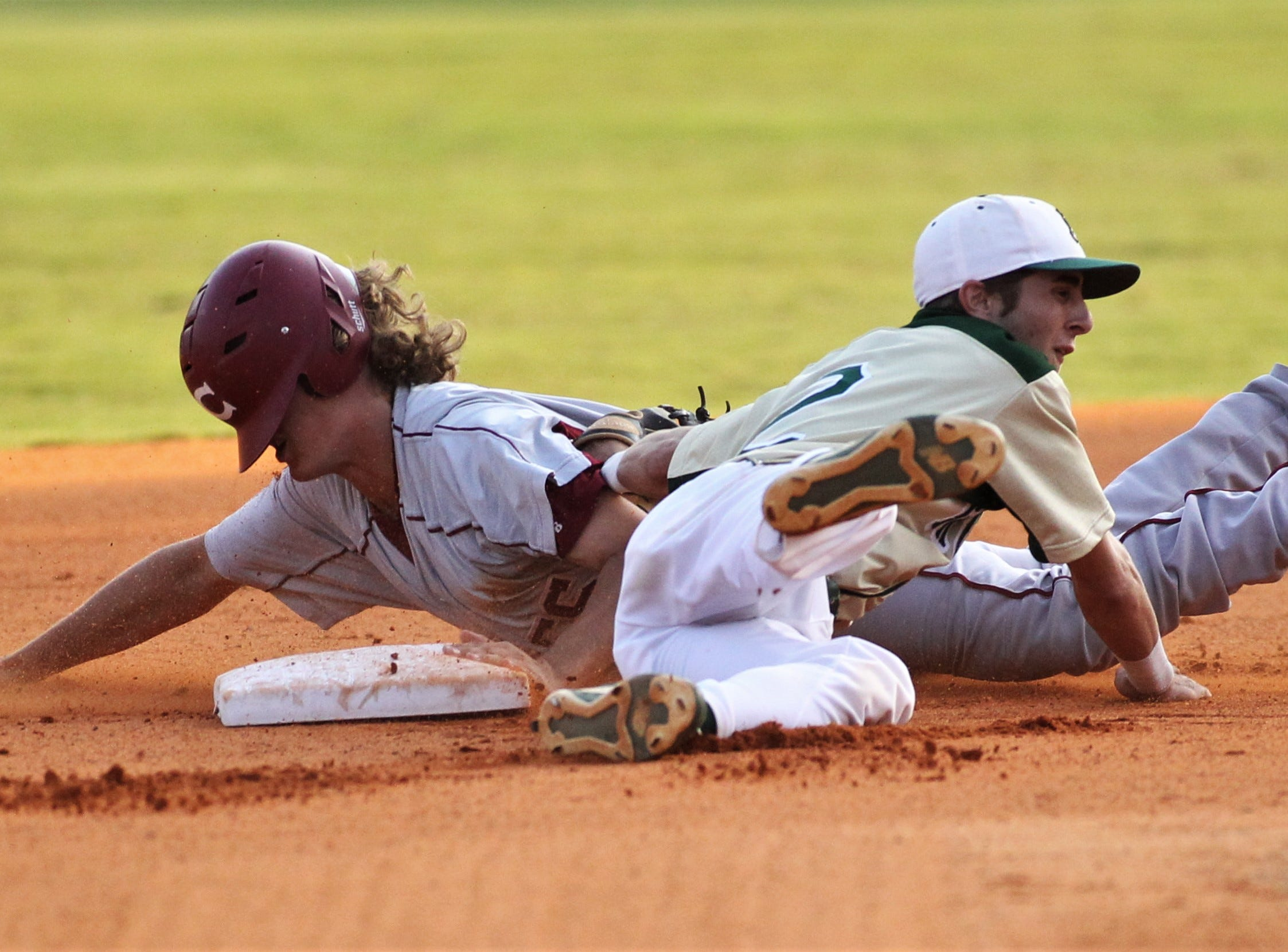 Chiles sophomore Tyler Gerteisen slides in under Lincoln shortstop Jackson White's tag for a stolen base as Lincoln baseball beat Chiles 5-4  in 10 innings during a District 2-8A championship game on Thursday, May 9, 2019.