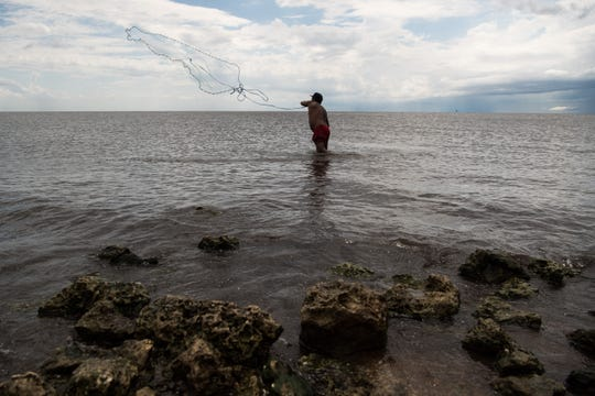 "Douglas Cruz, of West Palm Beach, casts for tilapia in the shallow waters of Lake Okeechobee on Tuesday, May 7, 2019, at Port Mayaca. Cruz was spending the day at the lake with partner Angela Rodrigues and her daughter, Daniela Matute, 3. ""She's autistic,"" Rodrigues said of her daughter, adding that being at the lake is more calming for her than the ocean."