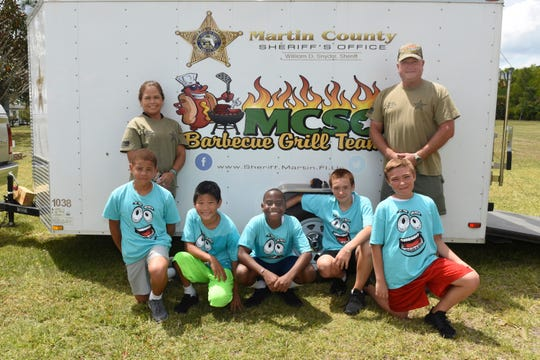 Martin County Sheriff's Office Grill Team at the Samaritan Center for Young Boys & Families' Field Day.  Pictured are, from left, standing, Thely Murphy, supervisor of the Crossing Guard Unit and Deputy Sheriff William R. Weiss, head of the Grill Team, with Samaritan Center residents, kneeling, Aiden, Landon, Isaac, Aiden and Tristan.