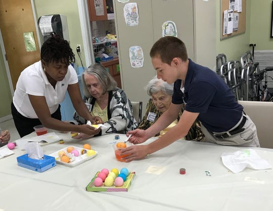 An aide at Alzheimer's Community Care, left, watches patients Joan Cayer and Monica Johnson paint Easter eggs with Aiden, a Samaritan Center for Young Boys & Families' resident.