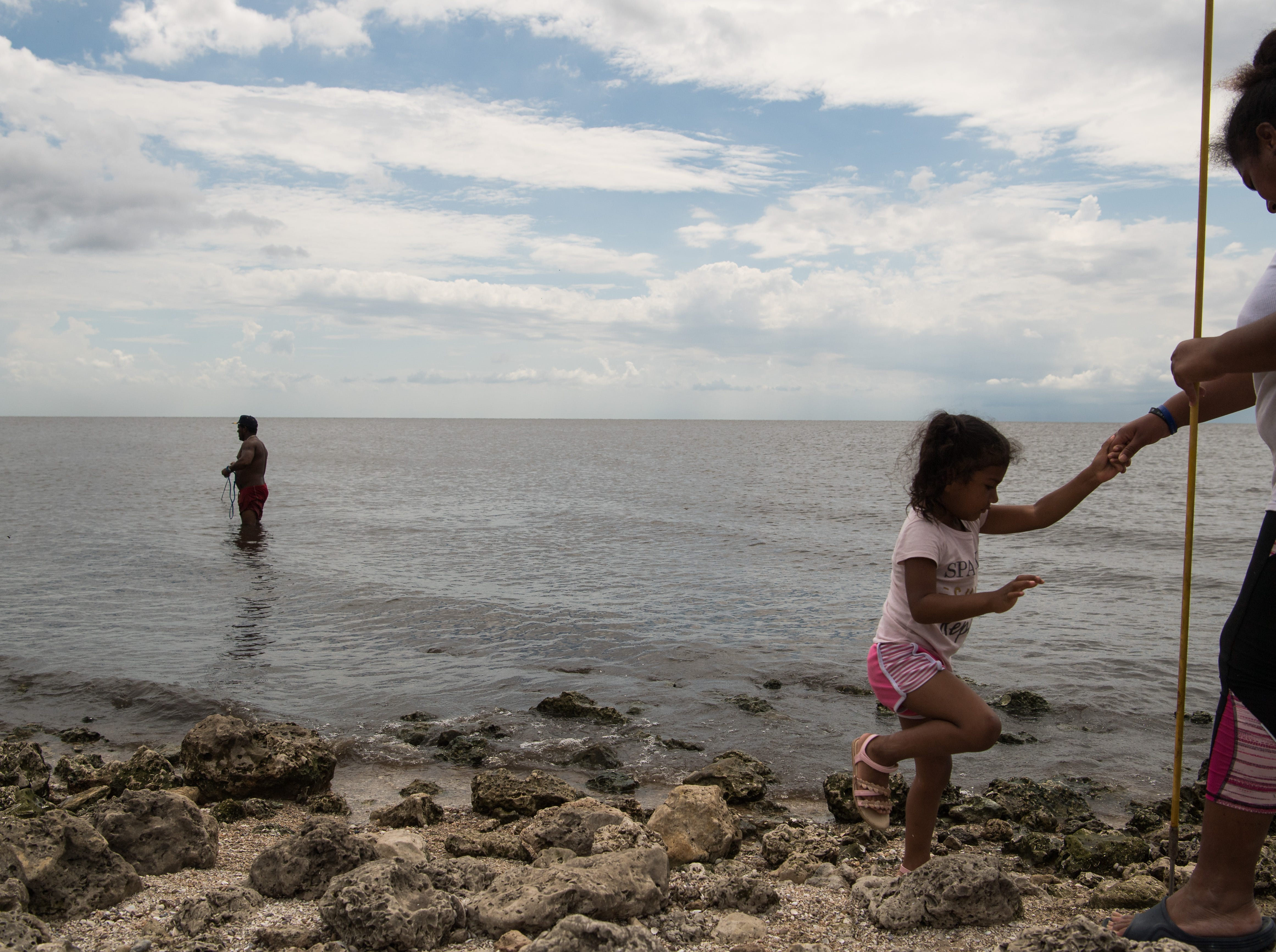 """Douglas Cruz (left), of West Palm Beach, casts for tilapia in the shallow waters of Lake Okeechobee on Tuesday, May 7, 2019, at Port Mayaca. Cruz was spending the day at the lake with partner Angela Rodrigues (right) and her daughter, Daniela Matute, 3. """"She's autistic,"""" Rodrigues said of her daughter, adding that being at the lake is more calming for her than the ocean."""
