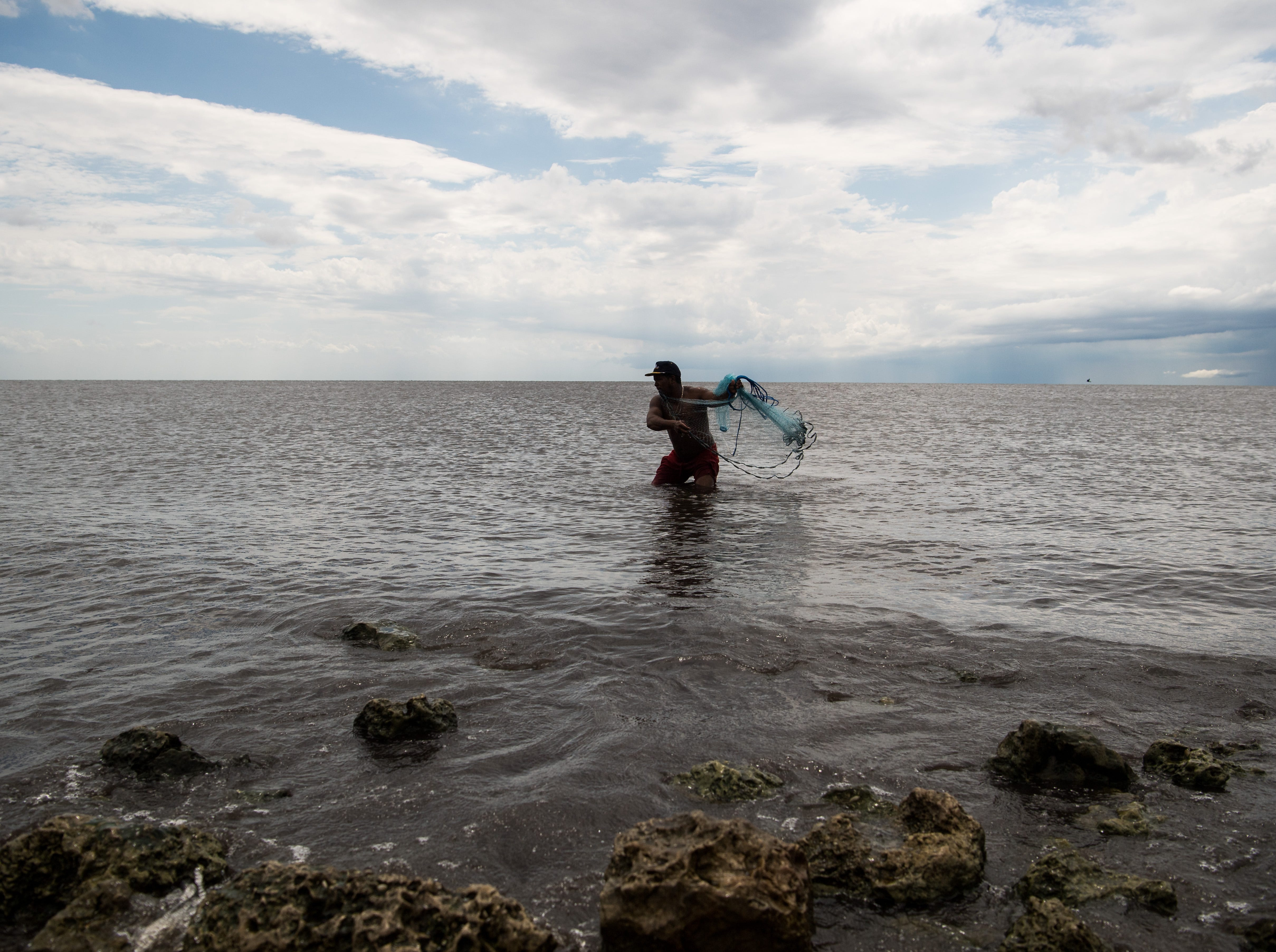 """Douglas Cruz, of West Palm Beach, casts for tilapia in the shallow waters of Lake Okeechobee on Tuesday, May 7, 2019, at Port Mayaca. Cruz was spending the day at the lake with partner Angela Rodrigues and her daughter, Daniela Matute, 3. """"She's autistic,"""" Rodrigues said of her daughter, adding that being at the lake is more calming for her than the ocean."""