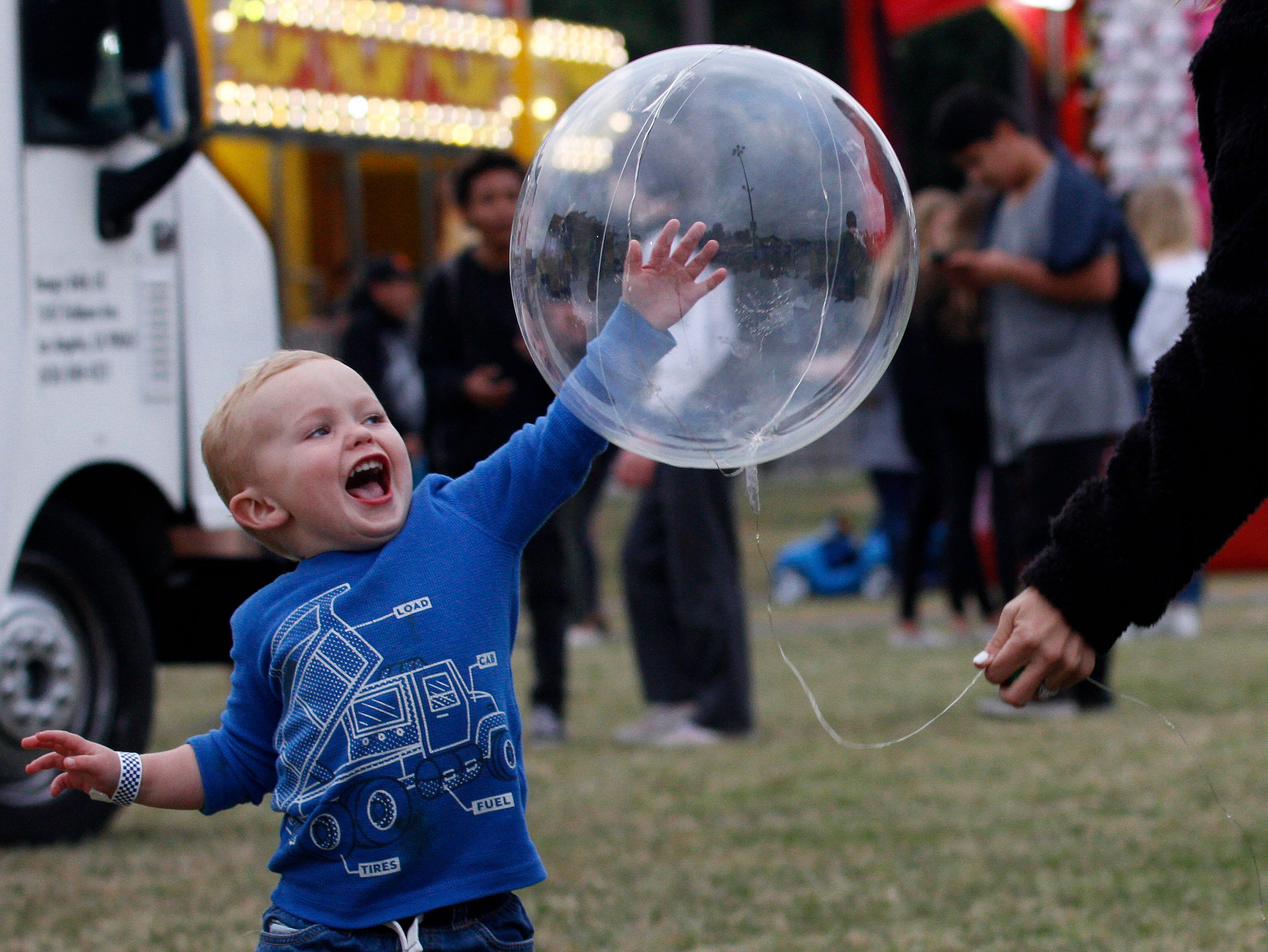 Grant Diegel tries to hit a balloon held by his mother, Alison Diegel, on Thursday during the opening night of the four-day Conejo Valley Days festival in Thousand Oaks.