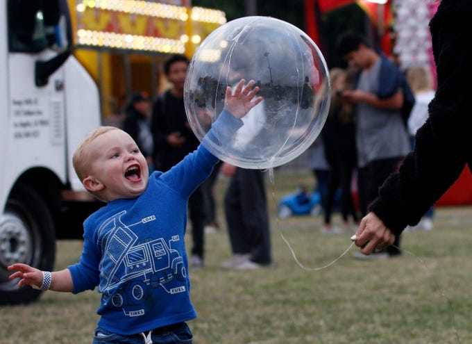 Grant Diegel tries to hit a balloon held by his mother, Alison Diegel, on May 9, 2019, during the opening night of the four-day Conejo Valley Days festival in Thousand Oaks.
