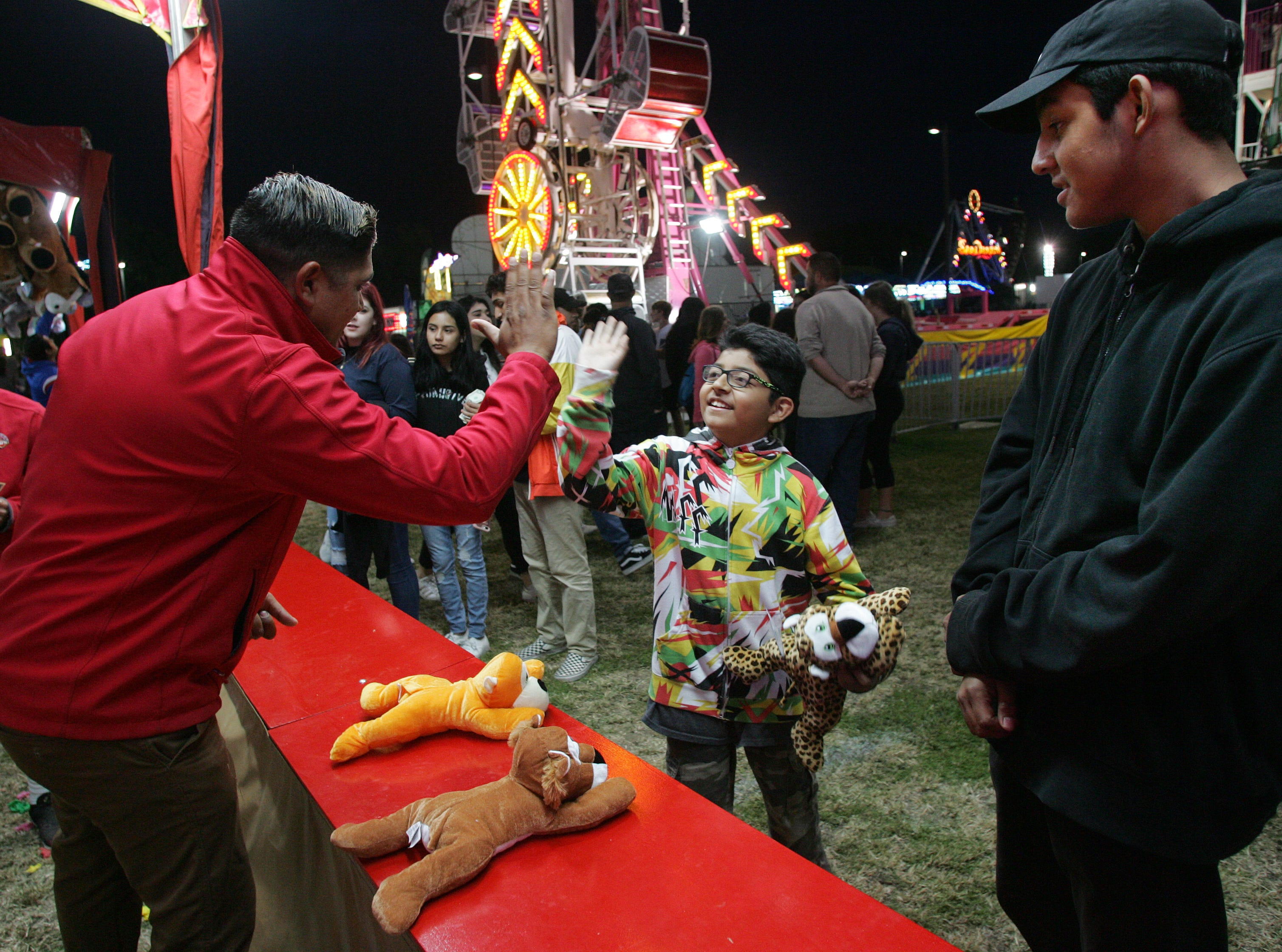 Martin Ascencio receives a high-five from vendor Dimitri Ederies as Erik Hernandez, right, watches. Ascencio won a prize at the carnival Thursday during the opening night of the four-day Conejo Valley Days festival in Thousand Oaks.