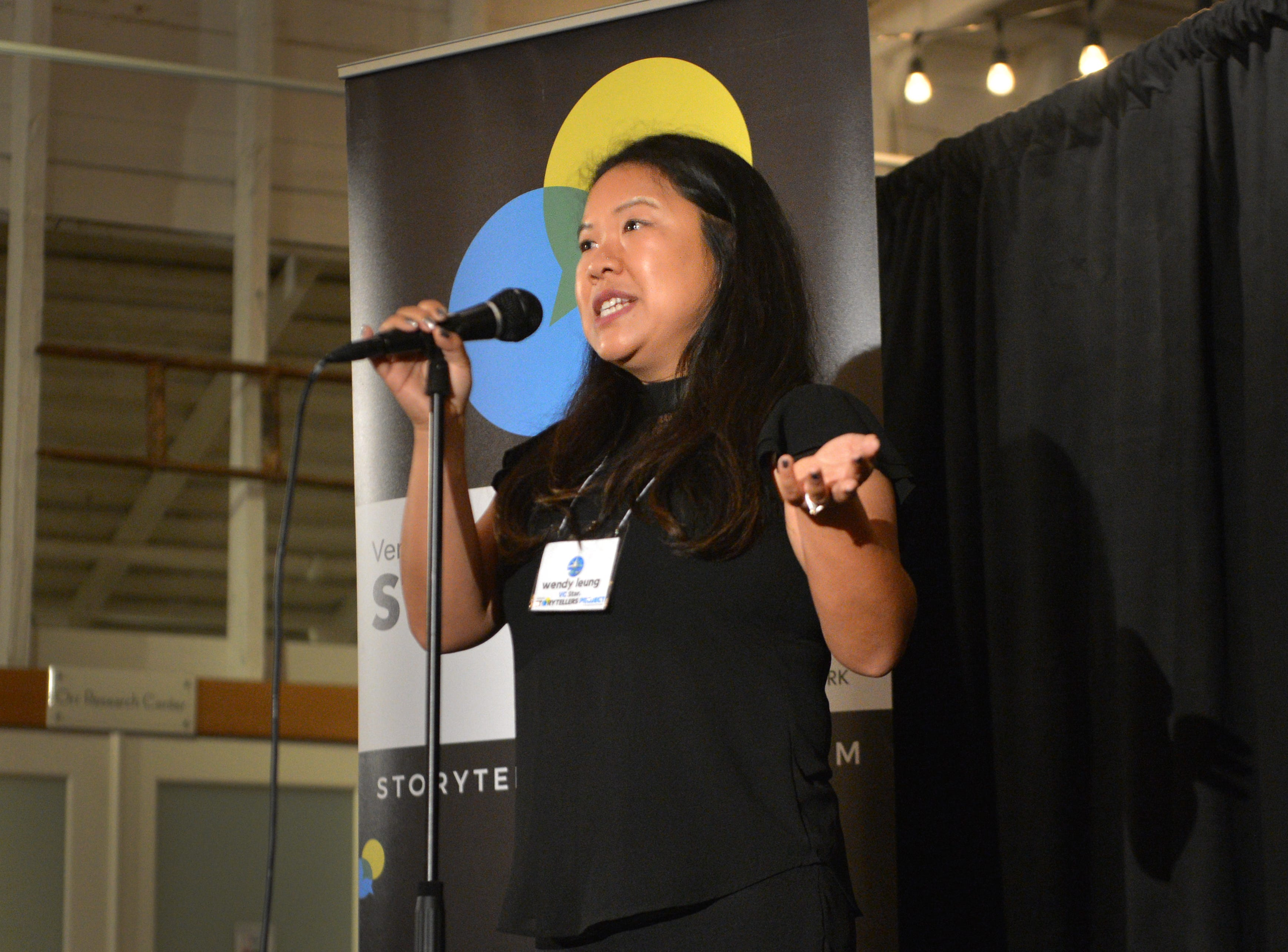 """Ventura County Star reporter Wendy Leung makes opening remarks as the emcee of the Ventura Storytellers Project event at the Museum of Ventura County Agriculture Museum on Thursday. The theme of the night was """"Away We Go."""""""