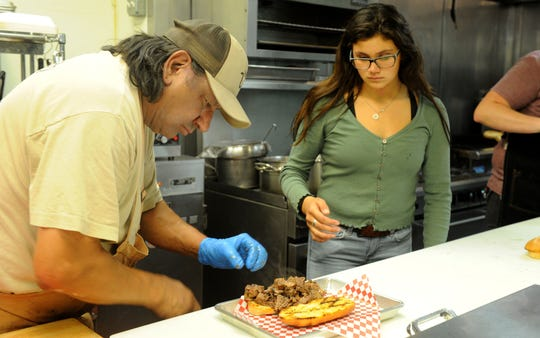 Tenaya Romero, 15, waits to deliver a brisket sandwich prepared by her father, Ernest Romero, at the family-owned J Wolf Catering & BBQ in Ventura. The Romeros' restaurant is returning to the dining scene nearly a month after matriarch Misty Romero underwent open-heart surgery.