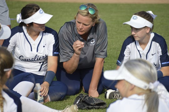 Central Valley Christian head softball coach Cindy Atherton talks to her players after the Cavaliers defeated California City on Thursday in a playoff game.