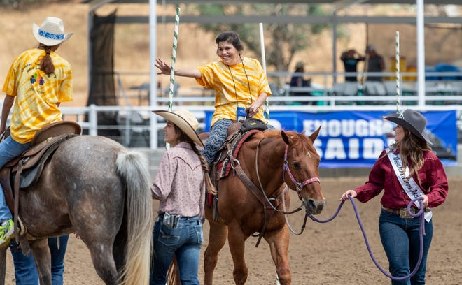 """Minnie Mejia waves to a friend from a horse led by Chloe Boling during the first """"High-Five Rodeo"""" at the Woodlake Rodeo Grounds on Friday, May 10, 2019. Participants from Exeter's Center for Discovery and Learning were paired up with real-life cowboys and cowgirls and other performers to experience modified rodeo-related stations in the rodeo arena."""