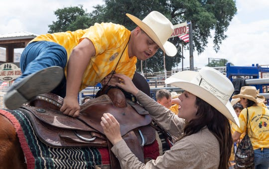 """Mallory McLaughlin, right, helps participants mount a horse during Woodlake Rodeo first """"High-Five Rodeo"""" on Friday, May 10, 2019. Participants from Exeter's Center for Discovery and Learning were paired up with real-life cowboys and cowgirls and other performers to experience modified rodeo-related stations in the rodeo arena."""