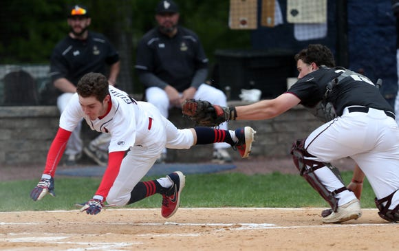 Kennedy's Andrew Guihan (18) dives around Iona catcher John Nowak (10) as he scores in the first inning during action at Kennedy Catholic in Somers May 9, 2019. Kennedy won the game 5-4.