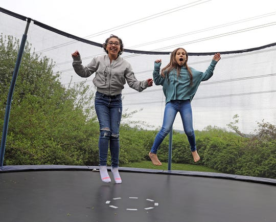 Bella Munoz bounces on the trampoline with her younger sister Natalie in Stony Point May 9, 2019. Bella had her heart transplant a year ago. Now she's doing well in school and advocating for blood, organ, eye and tissue donation.