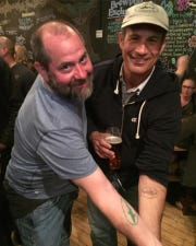 Brian Marine, left, of Wilmington, showing off his matching Dogfish Head tattoo with brewery co-founder Sam Calagione at the closing of Dogfish's original Rehoboth Beach brewpub in 2017.
